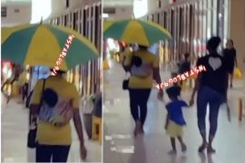Nursing Mother Uses Umbrella Inside A Shopping Mall